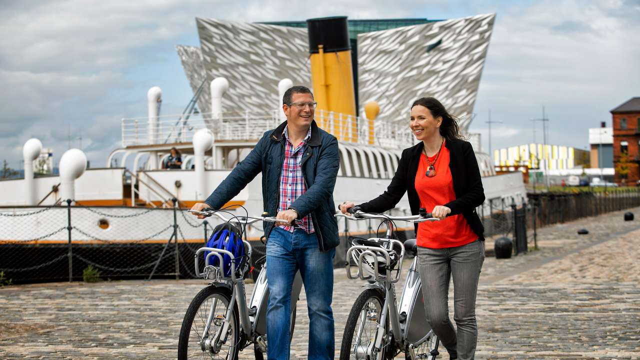 Annual Guide Cover Image 2018 - Couple walk bicycles by SS Nomadic in Titanic Quarter
