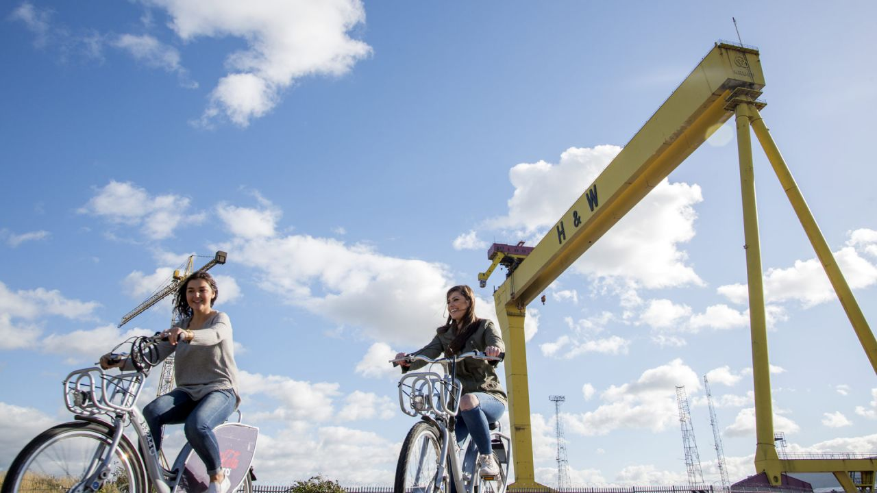 Friends ride Belfast Bikes near Harland and Wolff Cranes